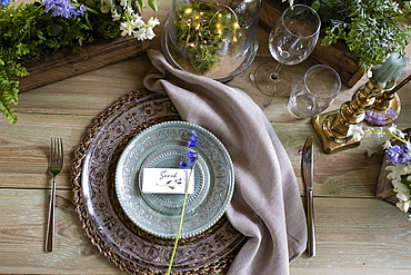 High angle close up of rustic place setting for a woodland naming ceremony.