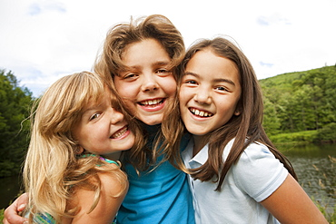 Three young girls, friends side by side, posing for a photograph in the open air, New York state, USA