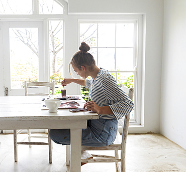 Teenage girl painting with watercolours in a light filled room