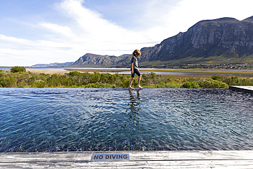 Eight year old boy walking around the edge of an infinity pool, a mountain backdrop