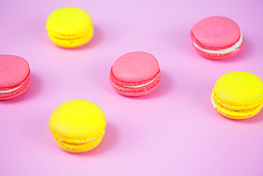 Pink and yellow macaroons, tasty sweet biscuits on a table.