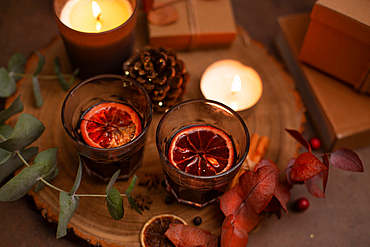 Christmas, wine glasses of mulled wine, lit candles and table decorations