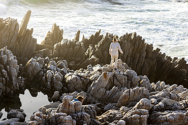 Two children exploring jagged rocks and rock pools by the ocean