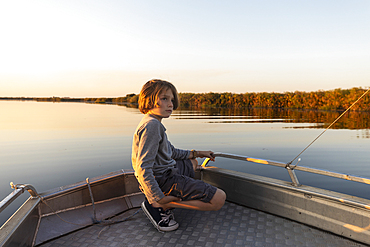 Young boy on a boat on the waters of the Okavango Delta at sunset, Botswana.