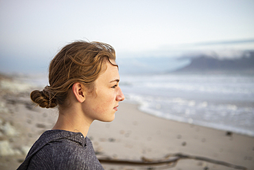 Profile portrait of a teenage girl looking out to sea from a beach at sunset.