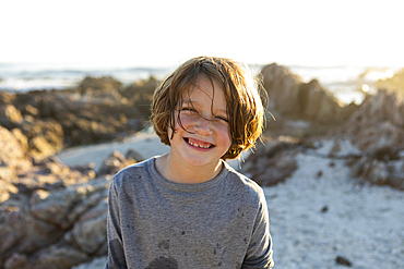 A young boy on the beach at sunset among the rocks of De Kelders.