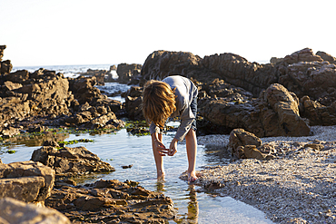 Young boy exploring a rock pool on the coast at sunset