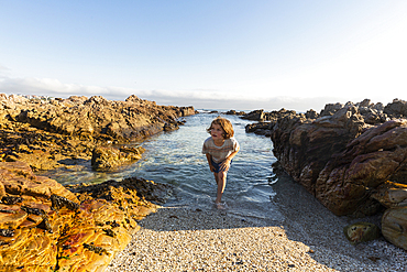 A young boy in shallow sea water among jagged rocks on the beach at De Kelders.