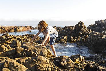 A young boy exploring the rock pools on a jagged rocky Atlantic Ocean coastline