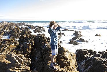 Boy exploring the jagged rocks and rock pools on the Atlantic Ocean coastline