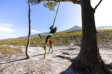 Teenage girl and younger brother using rope swing on a hiking trail