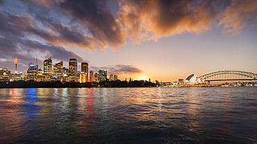 Sydney lit up at dawn seen from the water, including the Sydney Opera House.