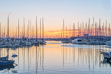 Boats moored in the harbour marina in Palermo at sunrise.