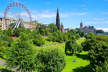 Ferris wheel and Scott monument in park in Edinburgh.