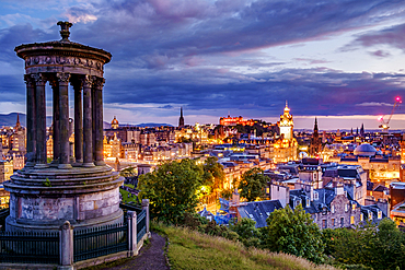 Calton Hill Folly and Edinburgh skyline lit up at dawn.