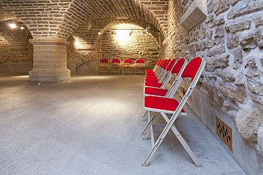 Chairs in a vaulted stone room for lectures meetings or seminars at a university