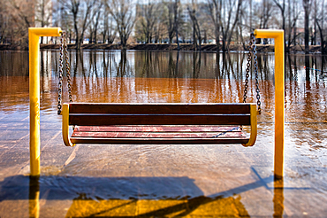Empty hanging bench swing surrounded by hard frozen ice, riverbank