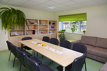 Modern day care nursery or pre-school kindergarten, spacious interiors, room with tables and chairs