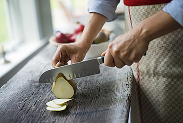 A woman slicing a fresh picked fruit, organic pear, Woodstock, New York, USA