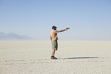 Man aiming hand gun, standing in vast, barren desert, Black Rock Desert, Nevada, USA
