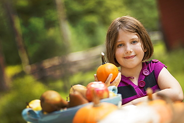 A young girl holding a pumpkin in her hand at a table outside. Harvest time, Woodstock, New York, USA