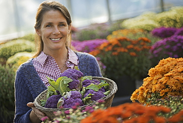 A woman holding a bowl of fresh produce, purple sprouting broccoli. Flowering plants. Crysanthemums, Woodstock, New York, USA
