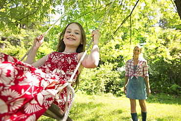 Summer. A girl in a sundress on a swing under a leafy tree. A woman standing behind her.