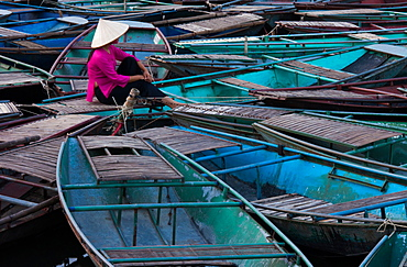 Lost in thought, a woman sits amidst a raft of boats. Ninh Binh, Vietnam, Ninh Binh, Vietnam
