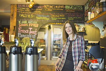 A coffee shop and cafe in High Falls called The Last Bite. A woman leaning on the counter, by the coffee machine, New York, USA