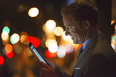 A man in a city at night, looking at a computer tablet, New York city, USA