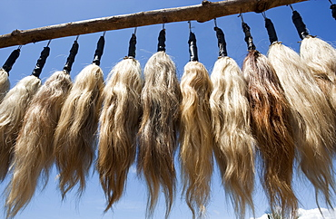 Plumes of human hair hanging from a frame against a blue sky, Togo, Africa