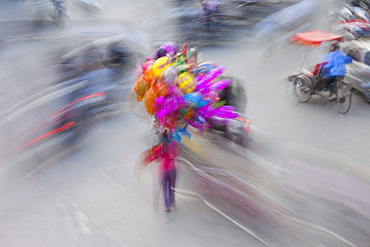 A busy street in Hanoi city, with motorscooter traffic and people with colourful balloons, Hanoi, Vietnam