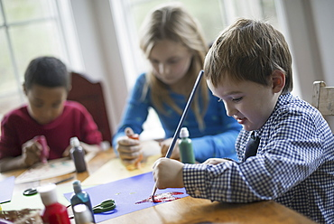 Children in a family home. Three children sitting at a table using glue and paint to create decorations, Woodland Valley, New York, USA