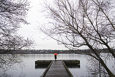 A woman standing at the end of a dock with an orange umbrella on a cloudy, grey day in Seattle, Seattle, Washington, USA