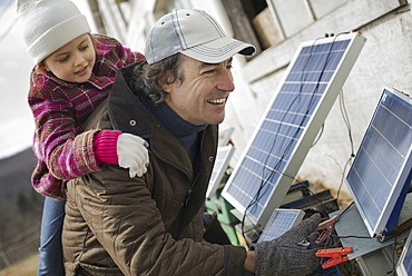 A man giving a child a piggybank while trying to connect the leads for solar power panels, Cold Spring, New York, USA