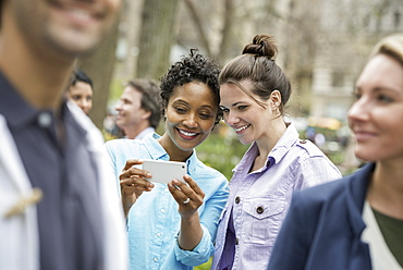 People outdoors in the city in spring time. New York City park. Two women in a group of friends, looking at a cell phone and smiling, New York city, USA