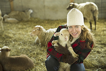 An Organic Farm in Winter in Cold Spring, New York State. A family working caring for the livestock. A woman holding a small lamb, Cold Spring, New York, U.S.A.