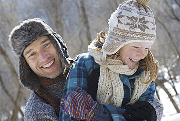 Winter scenery with snow on the ground. A young girl with a bobble hat and scarf and a man hugging her, Provo, Utah, USA