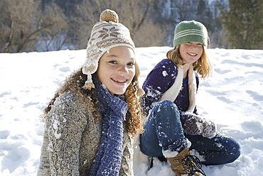 Winter scenery with snow on the ground. A woman and a child sitting on the ground laughing, Provo, Utah, USA