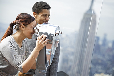 New York City. An observation deck overlooking the Empire State Building. A young couple looking through the telescope, New York city, USA