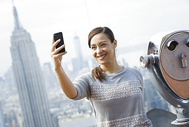 New York City. An observation deck overlooking the Empire State Building. A woman using her smart phone to take a photograph of herself and the view over the city, New York city, USA