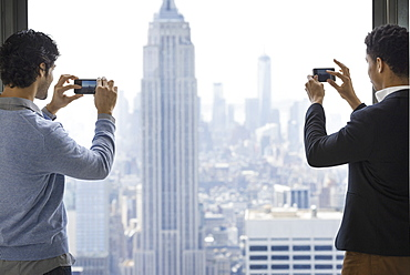 Urban lifestyle. Two young men using their phones to take images of the city from an observation platform overlooking the Empire State Building, New York city, USA