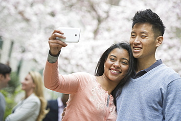 City life in spring. Young people outdoors in a city park. A couple taking a self portrait or selfy with a smart phone, New York city, USA