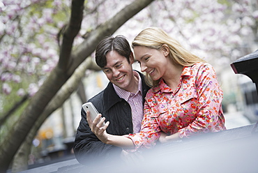 City life in spring. Young people outdoors in a city park. A young woman and man sitting side by side looking down at a smart phone, New York city, USA