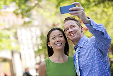A couple, a man and woman taking a selfy with a smart phone.