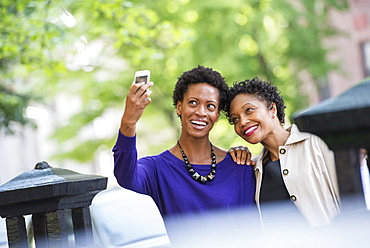 City life. Two women sitting on a park bench, side by side. Posing for a photograph with a smart phone.