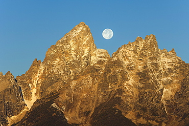 A jagged mountain range in the Grand Teton national park at night, with a full moon in the sky, Grand Teton National Park, Wyoming, USA