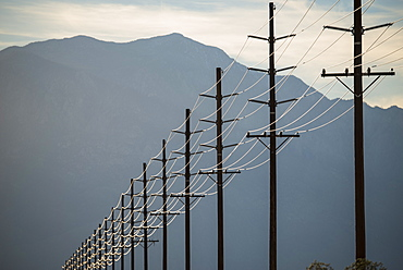 Power lines in rows across the landscape, against a mountain and sunset sky, California, USA