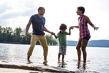 A family, parents and son spending time together by a lake in summer