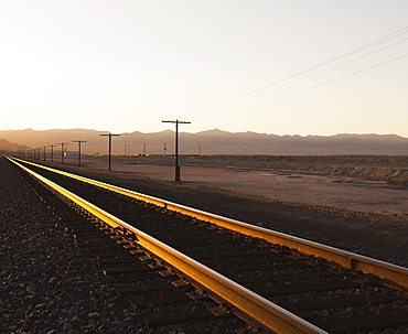 Railroad tracks extending across the flat Utah desert landscape, at dusk, Tooele County, Utah, USA